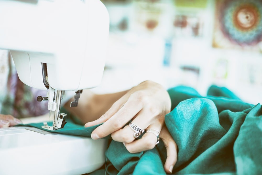 woman sitting at sewing machine sewing